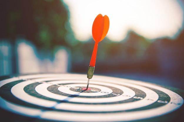 Bullseye or dart board has dart arrow hitting the center of a shooting target.