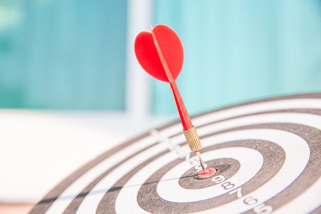Bullseye or dart board has dart arrow throw hitting the center of a shooting target.