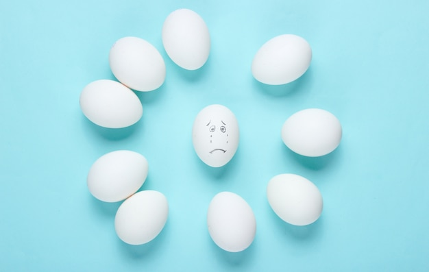 Bullying concept with eggs on a blue table. top view, minimalism