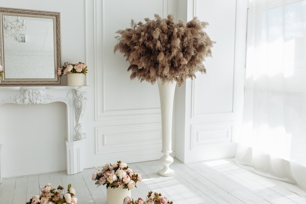 白い壁の背景に隔離された花瓶で、乾燥したアザミ、ゴボウ、リード、一般的なbulrush
