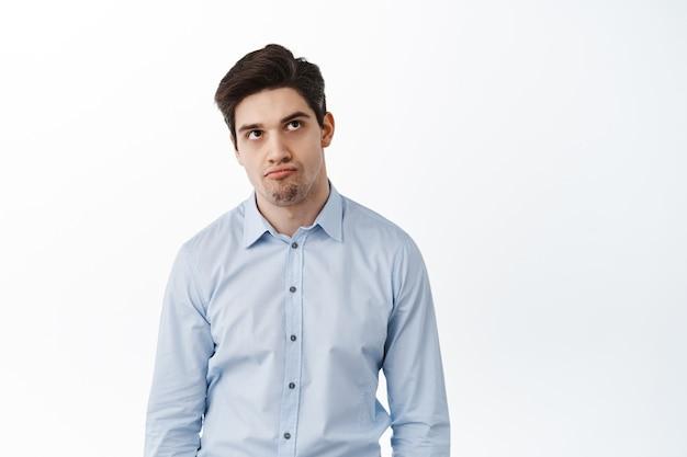 Облом. обеспокоенный и расстроенный офисный работник, менеджер компании с темными кругами под глазами, смотрит вверх с раздраженным и недовольным лицом, разочарованно стоит у белой стены