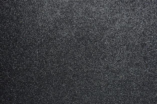 Bumpy black glitter textured background, closeup