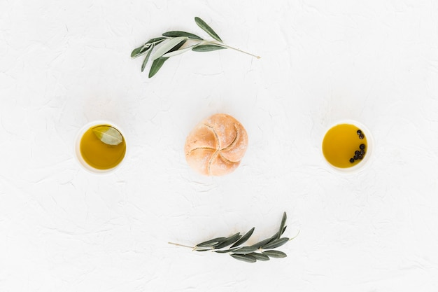 Bun between the black pepper and olive oil bowls on white background