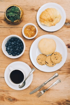 Bun; bread; cookies; jam; blueberries and coffee cup with cutlery on wooden backdrop