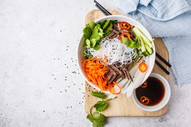 Bun cha salad bowl. vietnamese rice noodle with beef and chilli vegetables salad in white bowl