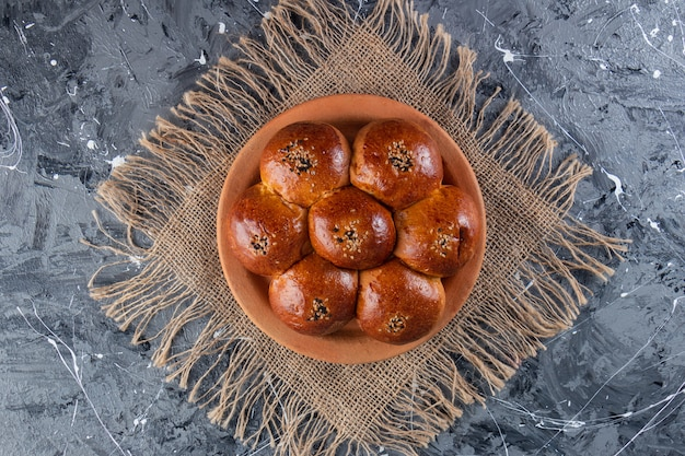 Camomilla panino con semi di papavero posto su un piatto di argilla
