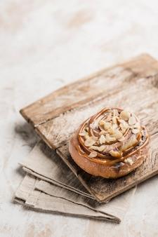 明るい背景にナプキンと木の板にキャラメルとアーモンドのスライスとパンシナボン。アメリカの古典的なパン。