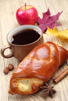Bun, cup of coffee and apple on wooden table