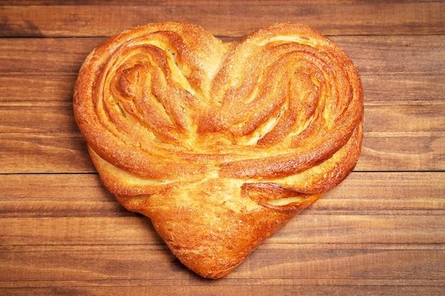 Булочка в сердечке с сахаром на деревянных фоне
