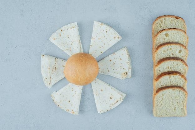 Булочка, лаваш и ломтики хлеба на каменной поверхности