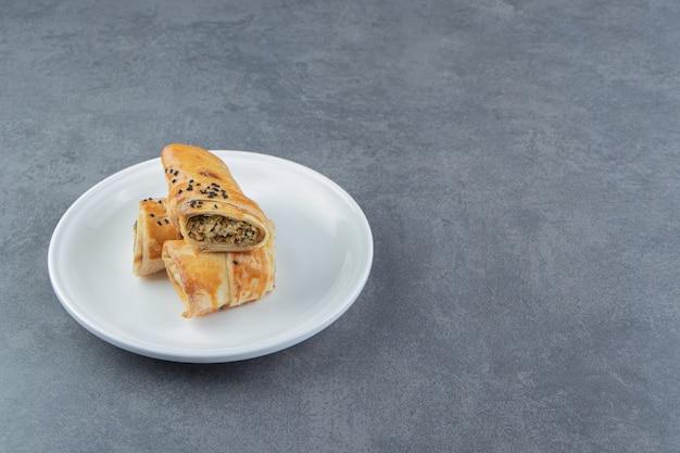 하얀 접시에 고기로 채워진 롤빵.