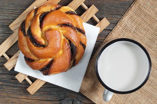 素朴な木製のテーブルにチョコレートクリームと牛乳のエナメルマグカップとパン