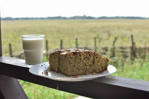 Булочка с маком запить стаканом молока. молоко в стакане и маковая лепешка на поле