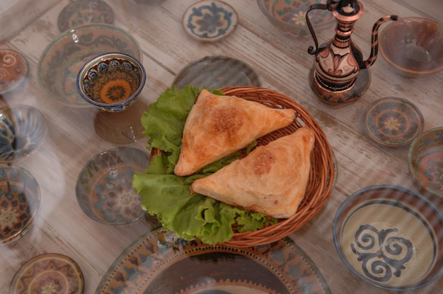 컵 세트의 배경에 있는 유리 표면에 고리버들 접시에 샐러드를 넣은 롤빵