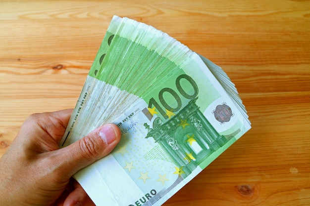 Bunch of 100 euro banknotes in man's hand with wooden table in the backdrop