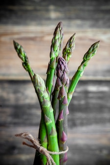 A bunch of asparagus on a dark wooden background. side view.