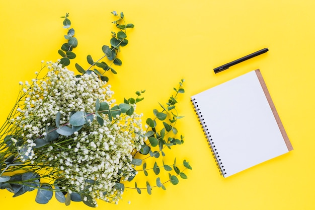 Bunch of baby's-breath flowers and spiral notepad with pen on yellow backdrop