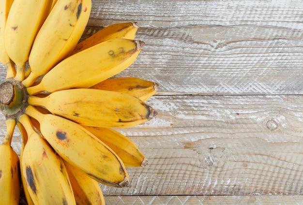 Mazzo di banane piatto giaceva su un legno