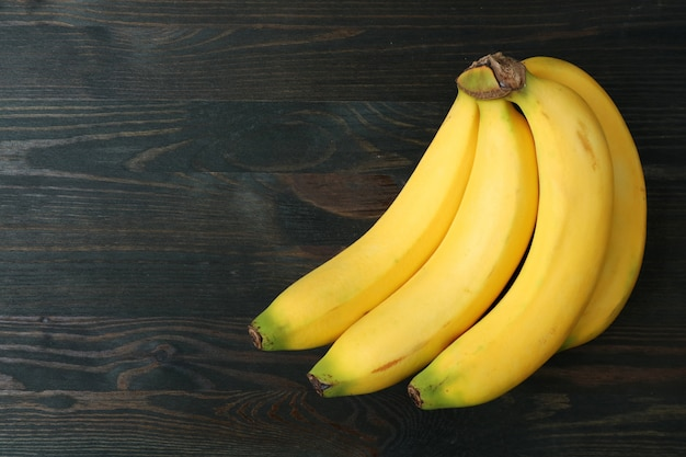 Bunch of bananas isolated on dark brown wooden table