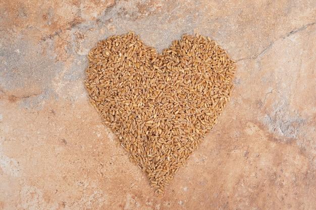 Bunch of barley formed like heart on orange background
