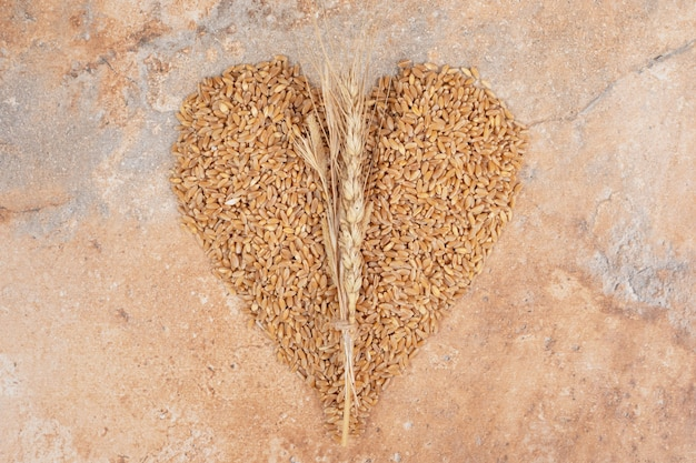 Bunch of barley formed like heart on orange background