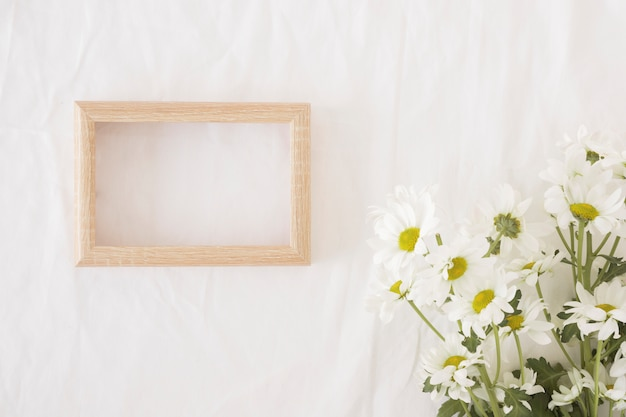 Bunch of beautiful flowers on green stems near photo frame