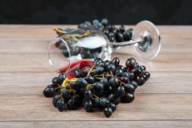 A bunch of black grapes and a glass of wine on wooden surface