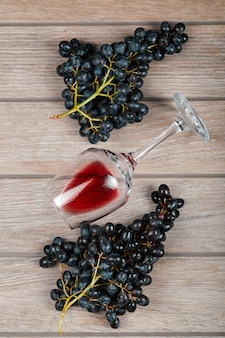 A bunch of black grapes and a glass of wine on wooden table