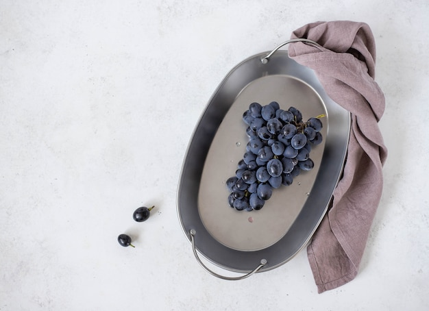 Bunch of blue grapes on a plate on a light background