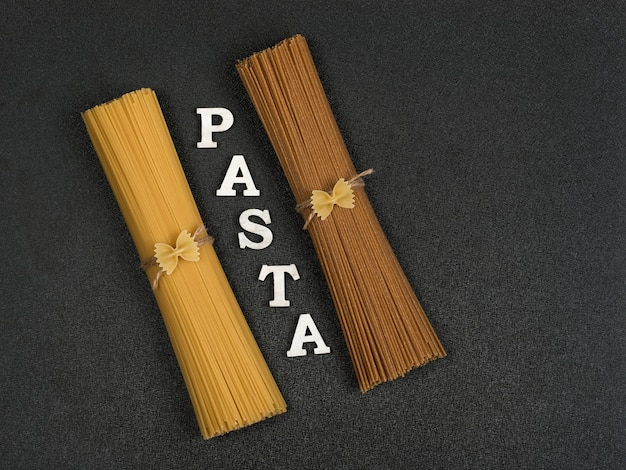 Bunch of brown and yellow pasta on grey background