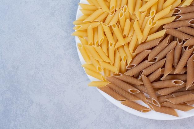 Mazzo di pasta di penne marrone e gialla sul piatto bianco