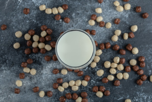 Bunch of cereal balls scattered around glass of milk.