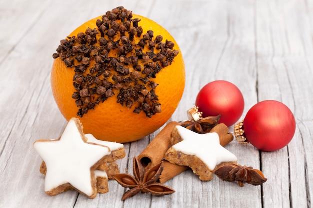 Mazzo di ornamenti natalizi e biscotti di panpepato su un tavolo di legno bianco