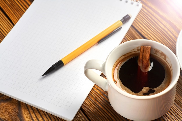A bunch of cinnamon knitted with a rope, a cup of coffee and a notebook