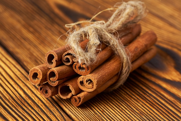 A bunch of cinnamon tied with a rope on wood