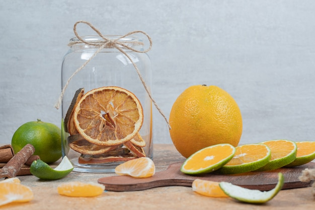 Bunch of citrus fruit slices on marble surface with cinnamon.