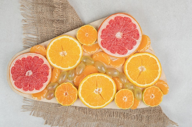 Bunch of citrus fruit slices on wooden board.