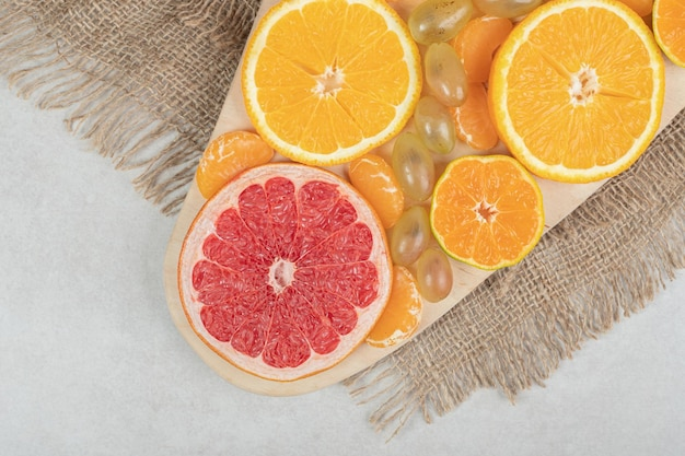 Bunch of citrus fruit slices on wooden board