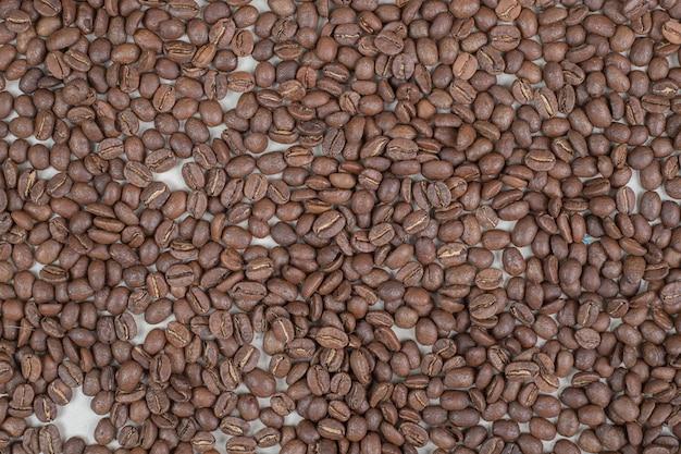 Mazzo di chicchi di caffè sulla superficie beige