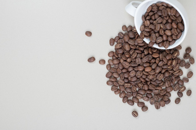 Bunch of coffee beans out of white mug