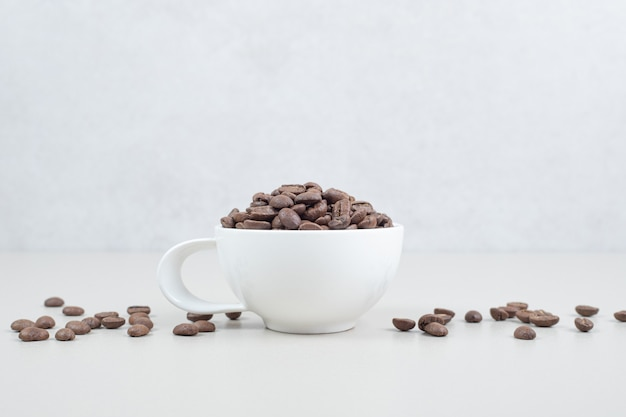 Bunch of coffee beans in white mug