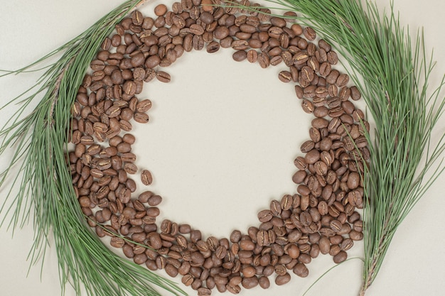 Bunch of coffee beans with branch on gray surface