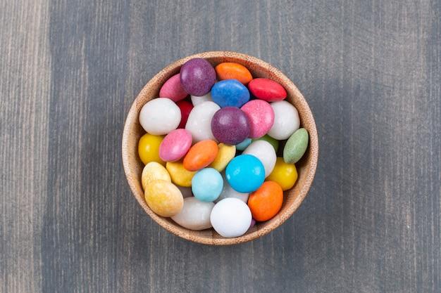 Mazzo di cioccolatini colorati in ciotola di legno