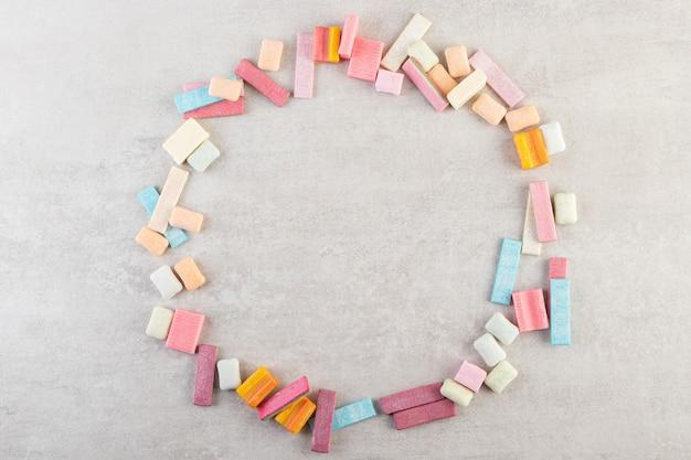 Mazzo di gomme da masticare colorate collocate sul tavolo di pietra.