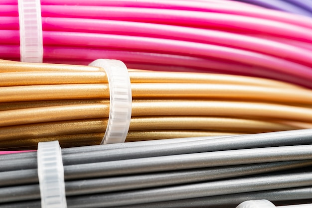 Bunch of colorful rolled cables. closeup of plastic bright wires for 3d printer lying indoors