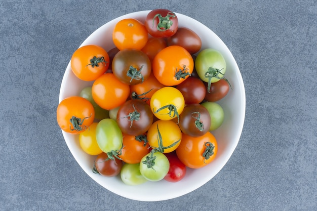 Bunch of colorful tomatoes in white bowl.