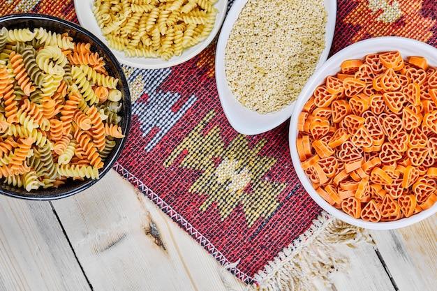 Un mucchio di ciotole di pasta cruda colorata sul tavolo di legno con panno intagliato.