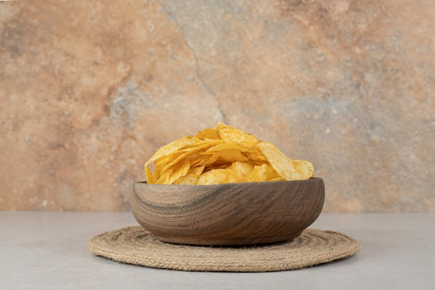 Bunch of crispy chips in wooden bowl
