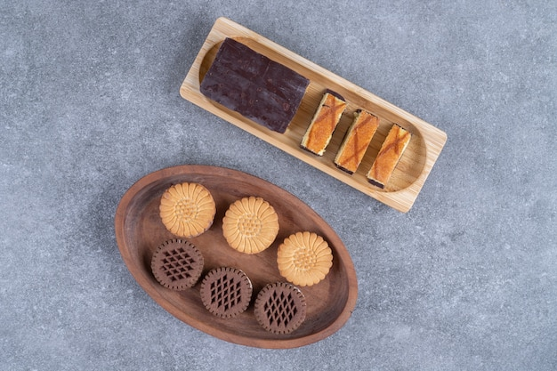 Bunch of delicious biscuits and cake slices on wooden plates