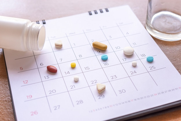 Bunch of different pills on a calendar background. concept healthcare